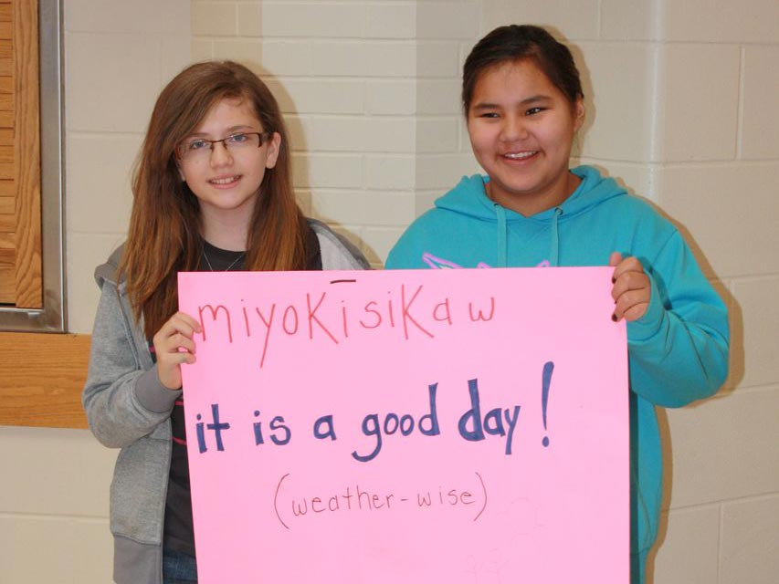 Students holding a sign written in Cree