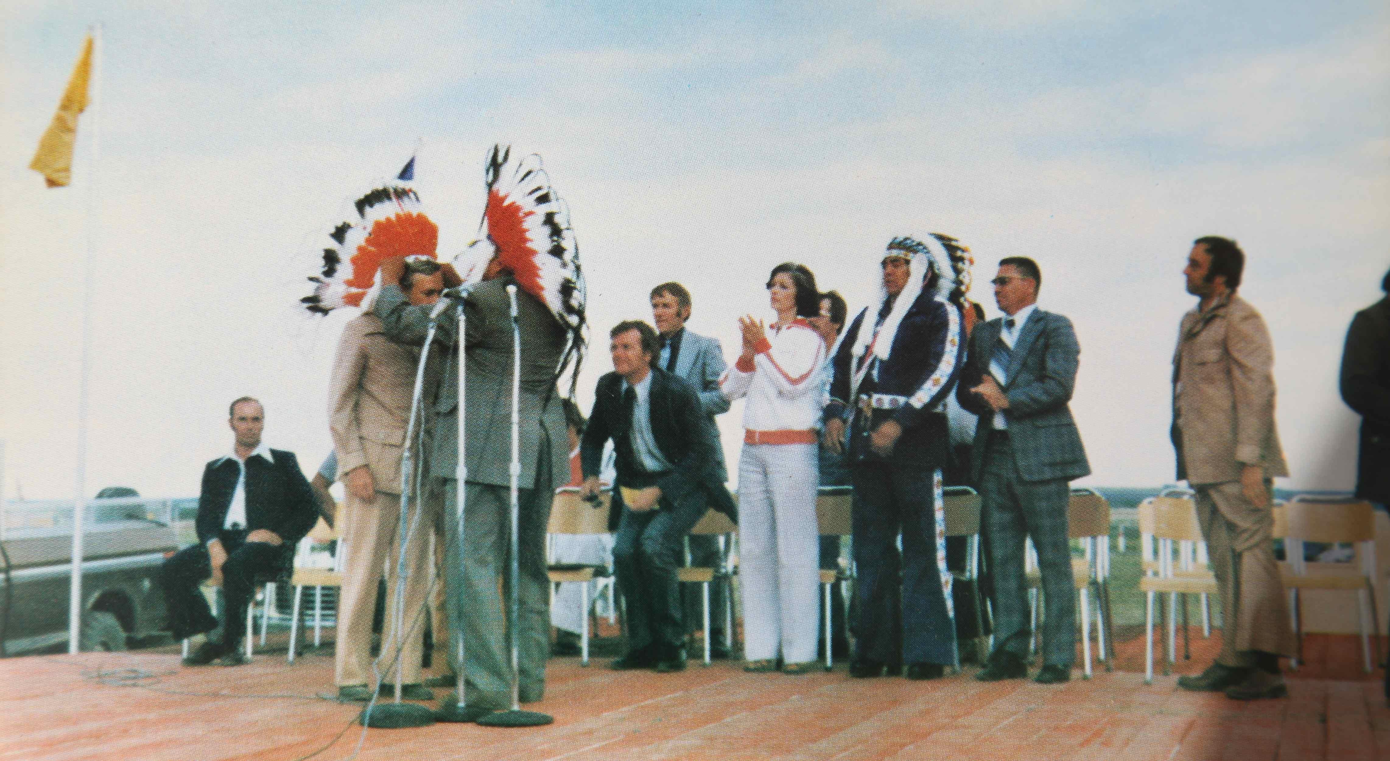 Premier Allan Blakeney receives Chiefs' Head-dress from Elder Adam Stevenson at the Saskatchewan Indian Summer Games, Cote Reserve, 1977.